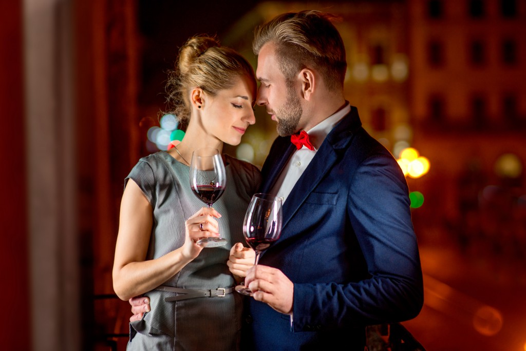 Man and woman holding glass with wine