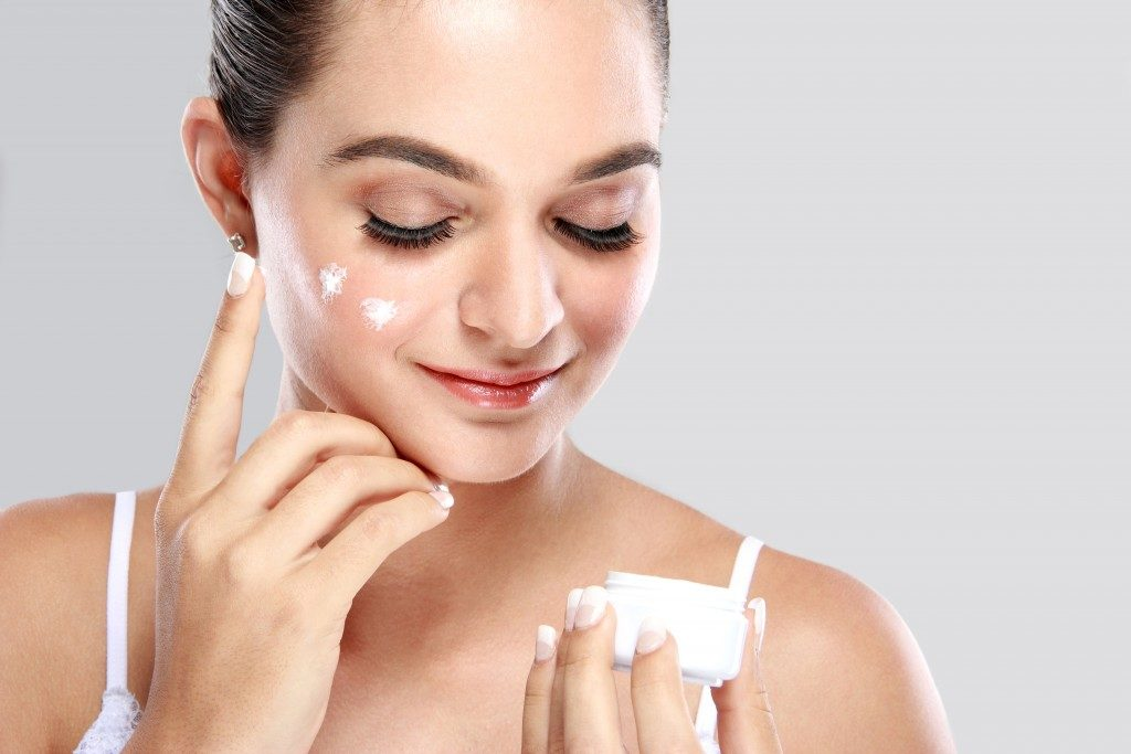woman putting moisturizer on face