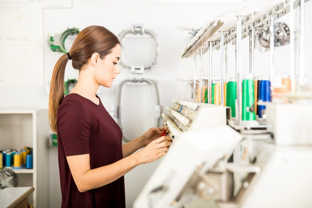 Woman operating an embroidery machine