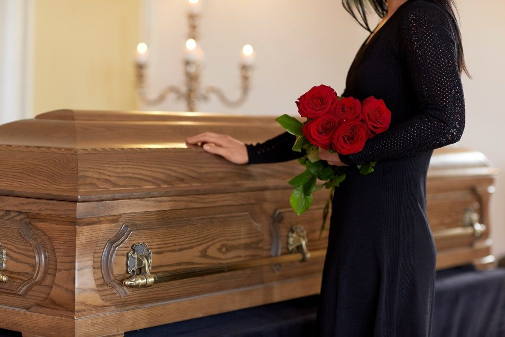 woman standing next to coffin