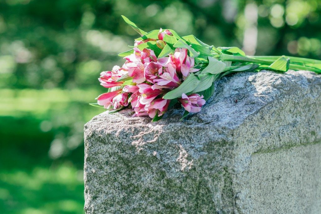 flowers on top of a cement headstone