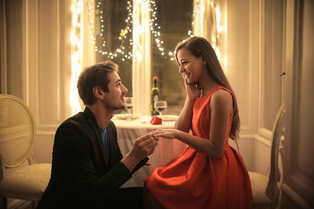 man proposing to his girlfriend in a private restaurant
