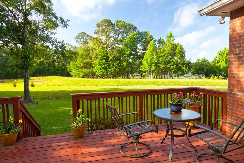 Residential backyard deck overlooking lawn and lake