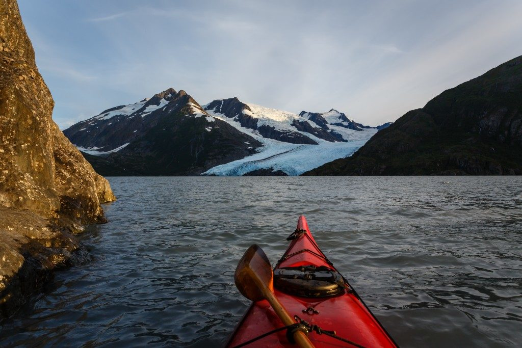 Kayaking to glacier in the Alaska wilderness on sunny summer day