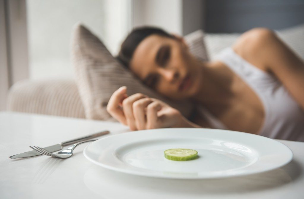 Woman lying in bed refusing to eat