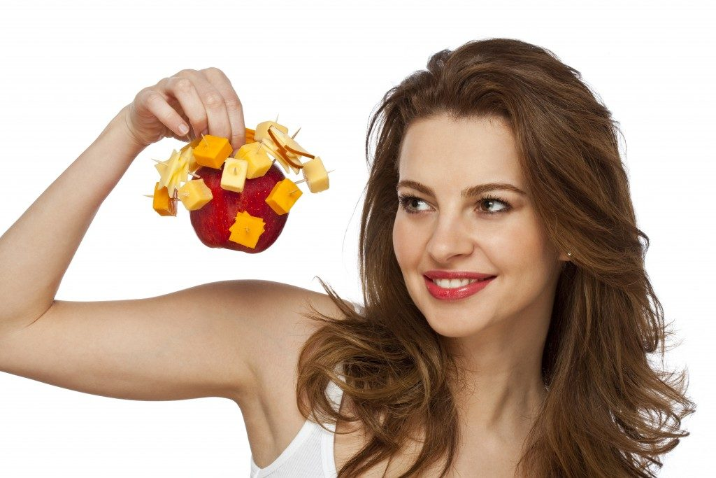woman holding an apple and cheese cubes