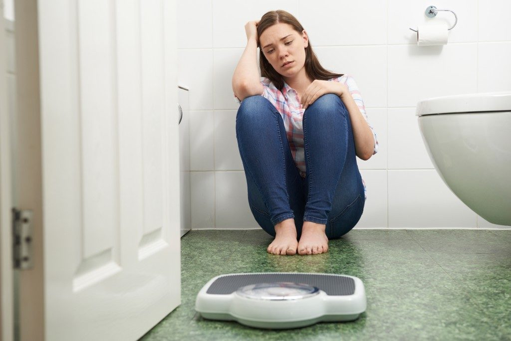 Teenage Girl Sitting On Floor Looking At Bathroom Scales