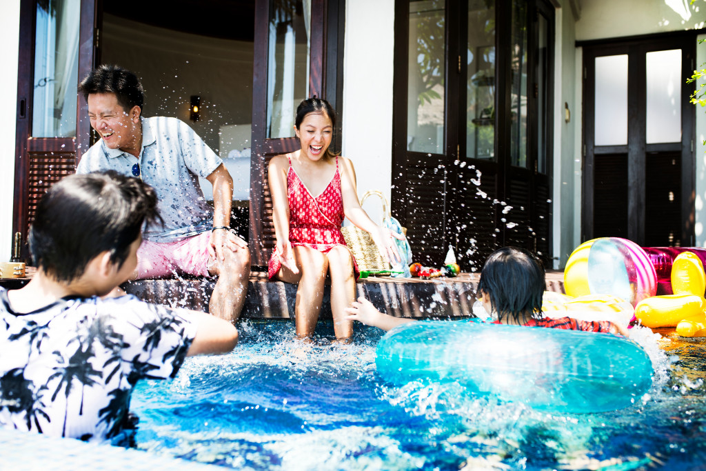 family at home swimming pool
