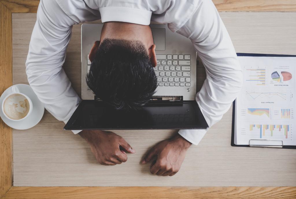 man sleeping on laptop